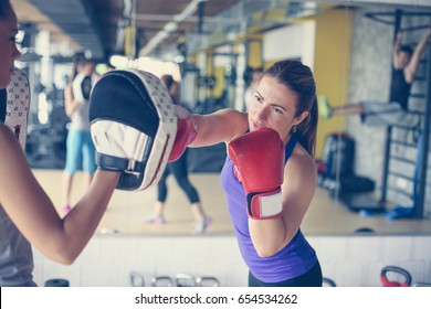 Woman boxer hitting the glove of his sparring partner. Woman workout in gym.