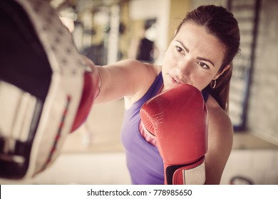 Woman boxer hitting the glove of his sparring partner.