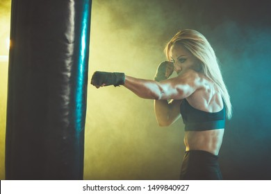 Woman boxer is training actively and hard, hitting a huge punching bag.