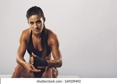 Woman boxer wearing black strap on wrist for boxing practice, Fitness female sitting getting ready for boxing practice. Beautiful young woman with muscular body preparing for workout.