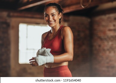 Woman boxer wearing strap on wrist for boxing practice. Fitness female getting ready for boxing practice. Beautiful young woman with muscular body preparing for workout looking away and smiling.