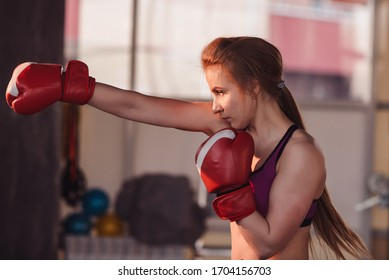 Woman Boxing close up. Portrait of a girl in the gym or at home who is boxing a punching bag.