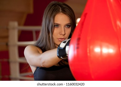 Woman in boxing gloves punching bag in studio