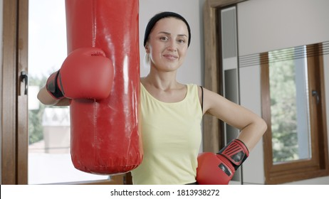 The woman is boxing at home. Woman with boxing gloves looking at camera and holding punching bag. Strong woman portrait.She smiles at the camera.