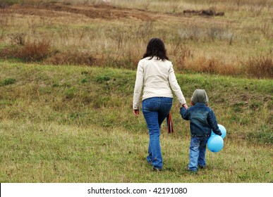 Woman and boy with blue balloon on the meadow escape
