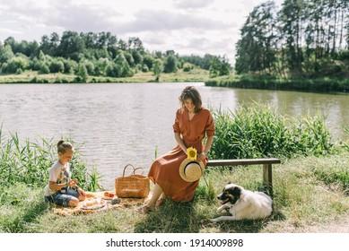 woman and boy sitting near lake with their dog, picnic basket near them