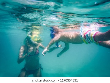 Woman and boy wearing mask and snorkel swimming underwater