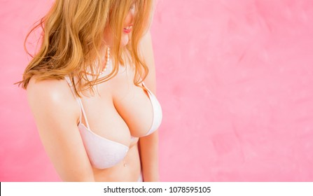 Woman in bra on pink background