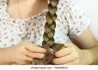 A woman braids a braid