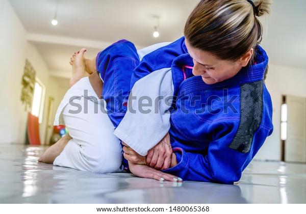 Woman in brazilian jiu jitsu bjj training judo kimura attack arm lock from the guard position submission attemp