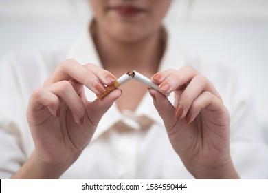 woman breaking cigarette to quit smoking; smoking ban or no smoking concept