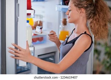 Woman breaking diet by taking cheesecake from fridge. Fridge full of groceries.