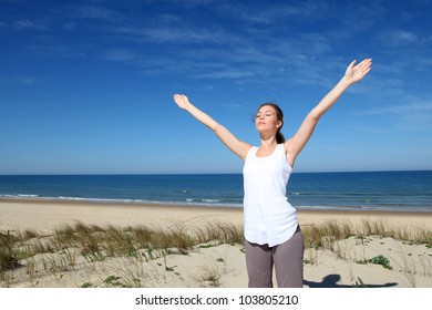 Woman breathing with arms up by the beach