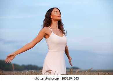 Woman breathing clean and fresh air in a wheat field