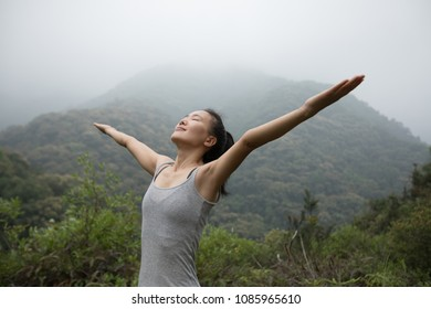 Woman breathing fresh air on morning mountain valley
