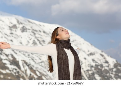 Woman breathing fresh air raising arms in winter with a snowy mountain in the background