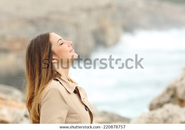Woman breathing fresh air in winter on the beach with the sea in the background