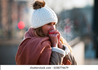 Woman breathing on her hands to keep them warm at cold winter day - Shutterstock ID 1038774679