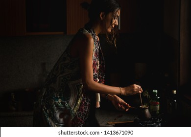 Woman brewing coffee Turk in the kitchen against window