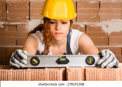 Woman Bricklayer with Helmet Holding a Spirit Level on a Brick Wall