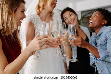 Woman in bridal gown toasting champagne glasses with friends. Bride in elegant wedding dress drinking champagne with her friends at wedding fashion shop.