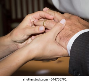 Woman bride holding groom's hand and putting on wedding ring for husband with closeup of hands in church