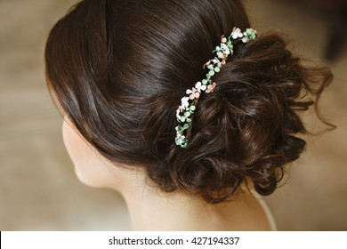 Woman, bride with magnificent hairdo. Hairdressing, jewellery in hair. Rear view, closeup. Studio, indoor