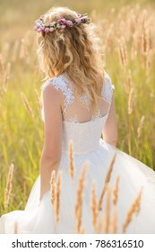 woman bridewith flower crown walking on summer field