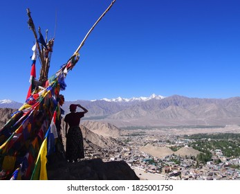 A woman with a bright blue sky and a colorful Talcho (Tibetan praying flags), Namgyal Tsemo Gompa, Leh, Ladakh, Jammu and Kashmir, India