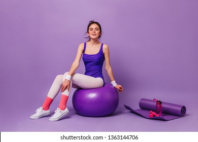 Woman in bright fitness bodysuit sits on fitball on background of yoga mat, pink water bottle and dumbbell