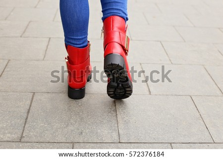 cd1f7f1b255b Woman in bright red leather ankle boots and blue jeans walking on the city  street. Street fashion look. Legs of a woman in winter boots - Image