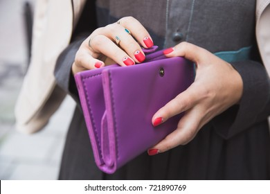 Woman with a bright red manicure and silver rings holds a large purple leather purse in her hands. Fashion and style, money and savings. Woman's hands with wallet