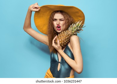 woman in bright swimsuit, pineapple, hat