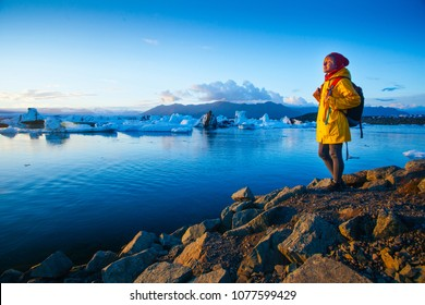 Woman in bright yellow raincoat near the Glacier Lagoon, Iceland