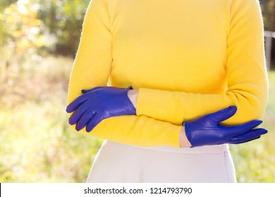Woman in a bright yellow sweater and blue gloves