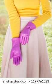 Woman in a bright yellow sweater and pink gloves