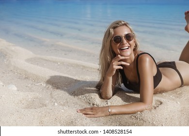 Woman brighten up beach white delighted smile. Attractive female tourist lie sandy beach ocean shore touch water feet wear black bikini wanna swim happily laughing look camera, relaxing