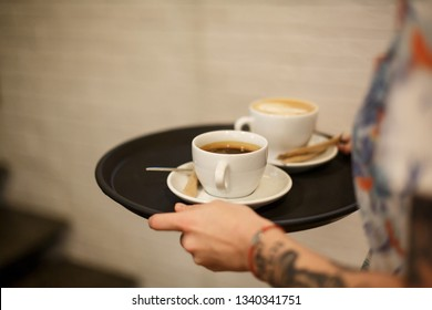 Woman bring two white cups of latte and americano coffe on tray.