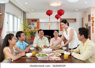 Woman bringing main dish to dinner table for Tet celebration; couplets with best wishes for coming year in the background