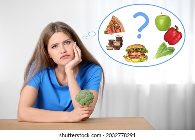 Woman with broccoli thinking about what to chose - healthy and unhealthy food at table indoors