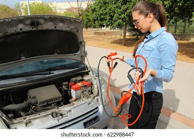 A woman with a broken car,  waits for assistance, Holds cables to the battery