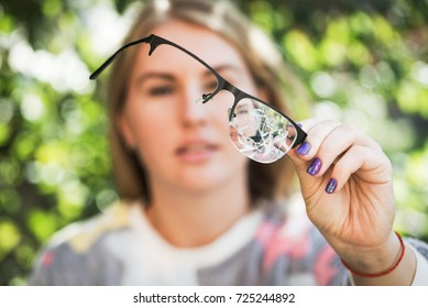 woman with broken glasses outdoors nature background.failure on a walk