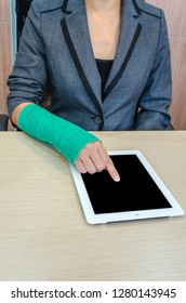 woman with broken hand and green cast  working on tablet computer in office
