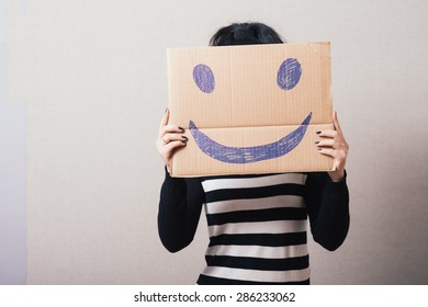 Woman with brown cardboard smiley. Gray background