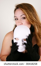 Woman with brown eyes and black gloves holds a blank white mask to her face