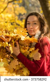 Woman with brown hair at autumn forest holding a yellow maple leafs