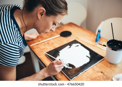 Woman with brown hair paining on canvas, she is wearing blouse with stripes