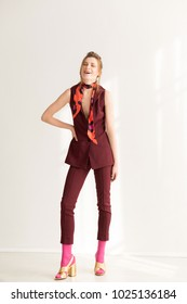 A woman with brown hair poses in a burgundy vest and pants, pink socks and gold sandals, clothing style 70's 80's.