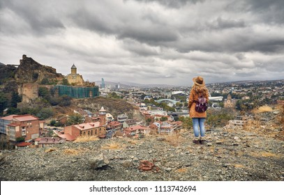Woman in brown hat and backpack looking at Old medieval castle Narikala with overcast cloudy sky in Tbilisi, Georgia