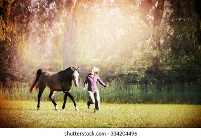 Woman and brown horse running across meadow with big trees
